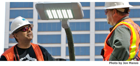 Two PG&E workers examine a new LED Streetlight
